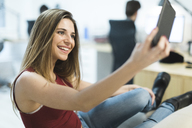 Smiling young woman using cell phone in the office - OCAF00225