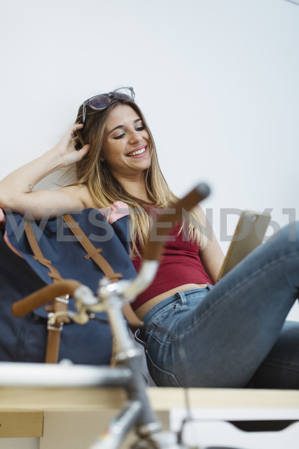 Smiling young woman using cell phone in the office - OCAF00234