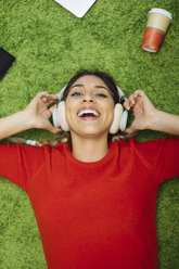 Happy young woman lying on carpet listening to music with headphones - OCAF00246