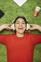 Happy young woman lying on carpet listening to music with headphones - OCAF00249