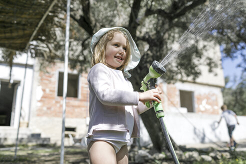 Smiling little girl playing with garden hose - KMKF00209