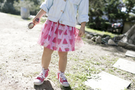 Little girl wearing fashionable skirt, partial view - KMKF00212