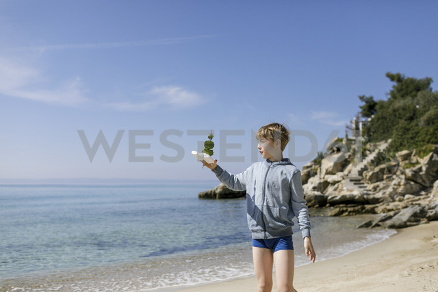 Boy standing on the beach with self-made toy boat - KMKF00218