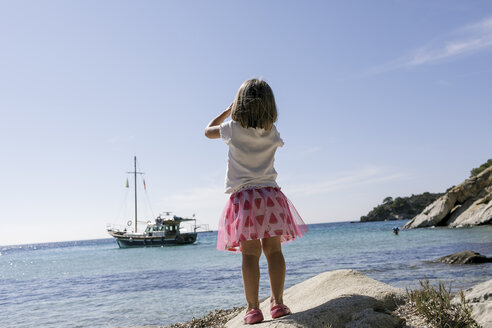 Back view of little girl with binoculars watching boat - KMKF00221