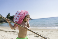 Little girl with stick playing on the beach - KMKF00224