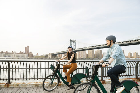 Happy couple cycling on footpath by Manhattan bridge against sky - CAVF45370