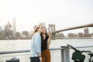 Man kissing happy woman photographing against East river in city - CAVF45376