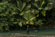 Full length of woman standing on rocks at lakeshore against tree in El Yunque National Forest - CAVF45385