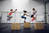 Side view of determined female athletes doing box jumping at health club - CAVF45499