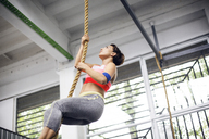 Low angle view of female athlete climbing rope at gym - CAVF45502