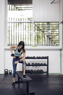 Determined female athlete lifting dumbbell at gym - CAVF45526