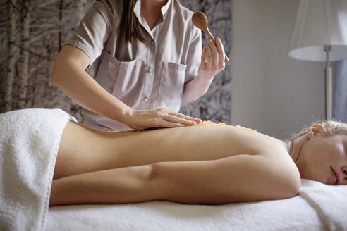 Midsection of massage therapist applying medicine on woman's back in spa - CAVF45583