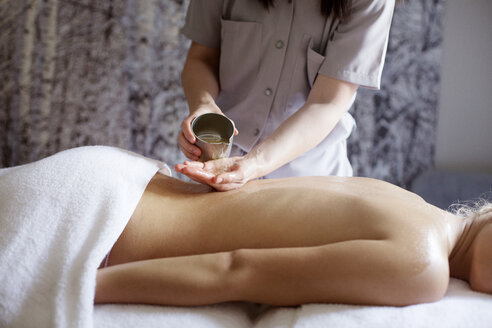 Midsection of female therapist pouring essential oil on woman's back in spa - CAVF45586