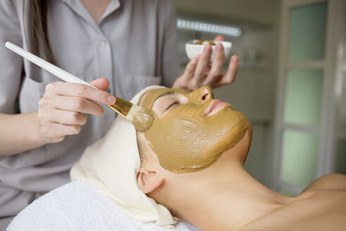 Female therapist applying facial mask on woman's face in spa - CAVF45601