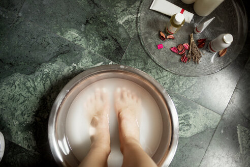 Overhead view of woman soaking feet in tub during pedicure in spa - CAVF45604