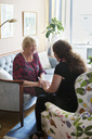 Cheerful grandmother talking to her granddaughter in living room - MASF06603