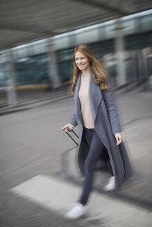 Confident businesswoman pulling suitcase at airport - PNEF00602