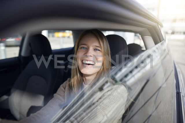Portrait of laughing young woman sitting in car - PNEF00617
