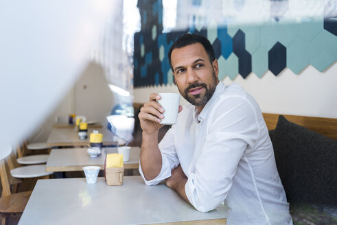 Man drinking coffee in a cafe - DIGF03930
