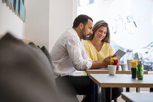 Young woman and man sharing tablet in a cafe - DIGF03933