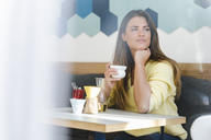 Young woman in a cafe holding cup of coffee - DIGF03936