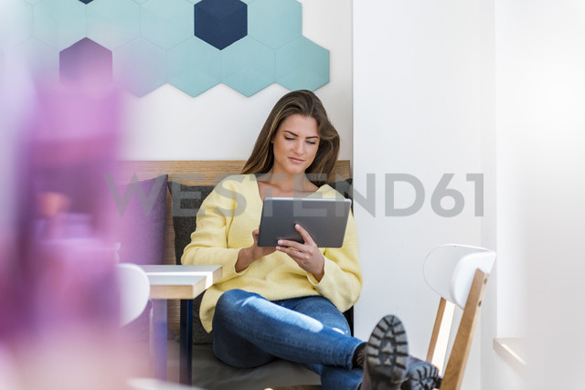 Relaxed young woman using tablet in a cafe - DIGF03939