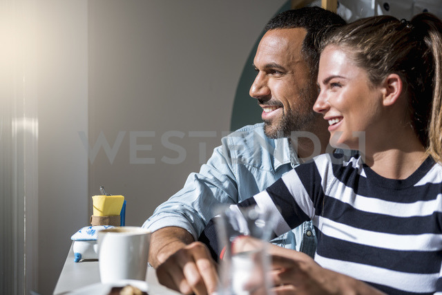 Happy couple in a cafe looking out of window - DIGF03945