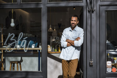 Smiling man standing at entrance door of a cafe - DIGF03948