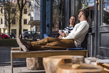 Man and woman sitting outside a cafe talking - DIGF03957