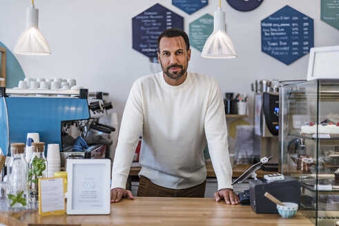 Portrait of confident owner behind the counter of a cafe - DIGF03960