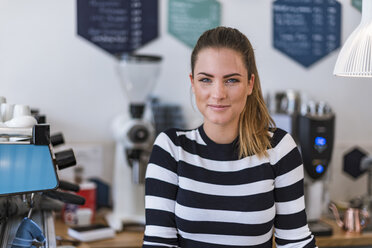 Portrait of smiling young woman in a cafe - DIGF03963