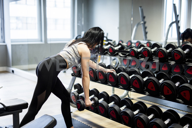 Woman exercising with dumbbells in gym - DAWF00613