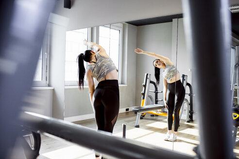 Woman exercising in gym looking in mirror - DAWF00625