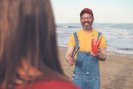 Happy man in dungarees on the beach offering soft drink to woman - RTBF01175