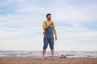 Bearded man drinking soft drink on the beach - RTBF01184