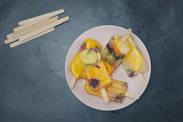Homemade orange and lemon popsicles with edible flowers on plate - SKCF00441