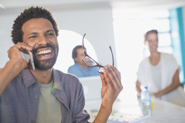 Laughing, enthusiastic businessman talking on smart phone - HOXF03387