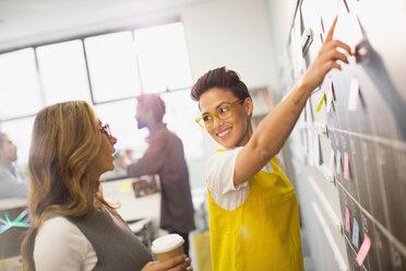 Creative businesswomen planning, scheduling at calendar blackboard - HOXF03390
