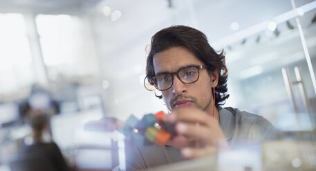 Focused, innovative male entrepreneur examining prototype in office - HOXF03444