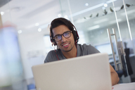 Portrait smiling, confident creative businessman with headphones at laptop in office - HOXF03459