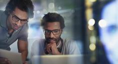 Businessmen using digital tablet and laptop - HOXF03474