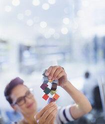 Curious, innovative female entrepreneur examining prototype - HOXF03486