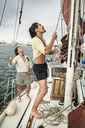 Man adjusting mast while traveling friend in sailboat - CAVF45743
