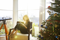 Girl using mobile phone while sitting on armchair by Christmas tree at home - CAVF45770