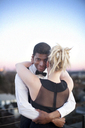 Portrait of man embracing girlfriend while standing in patio - CAVF45818
