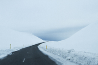 Empty country road amidst snowy field against cloudy sky - CAVF45842