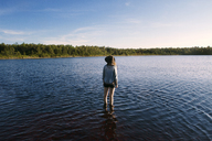 Rear view of woman standing in lake and looking at view - CAVF45878