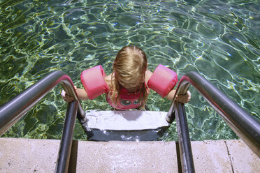 High angle view of girl by ladder in swimming pool - CAVF45923