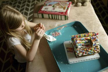 High angle view of girl decorating toy house - CAVF45929