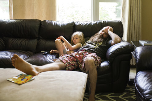 Girl looking away while sitting with father sleeping on sofa - CAVF45932